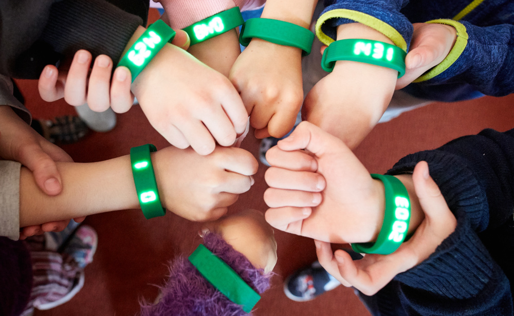 Kinder zeigen ihre Step Fit Armbänder