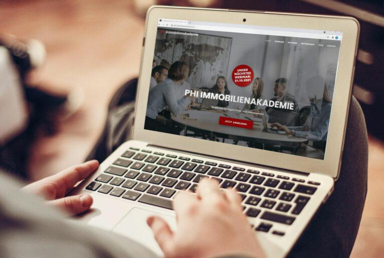 Laptop und Website der PHI Immobilienakademie